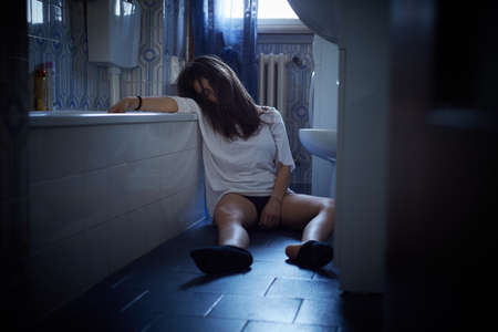 Girl addict unconscious sitting on the bathrooms floor Stock Photo