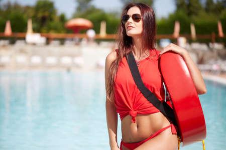 Beauty lifeguard woman posing in swimming pool