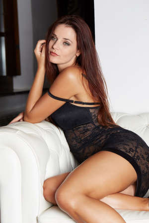 Beautiful sexy tanned blond woman with in black lace lingerie with a beautiful evening makeup on the sofa Stock Photo