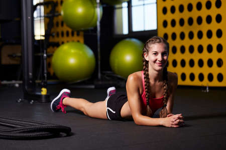 beautiful athletic woman relaxing after workout in gym