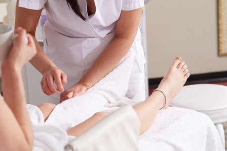 Female Enjoying Relaxing legs Massage In Cosmetology Spa Center Stock Photo