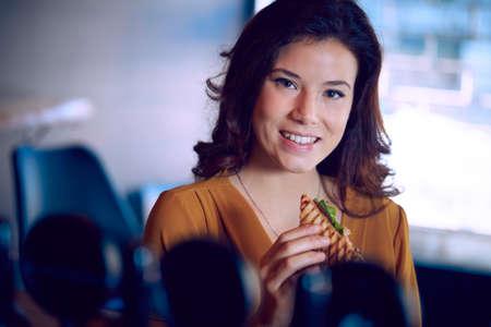 pretty woman eating club sandwich in a brewery