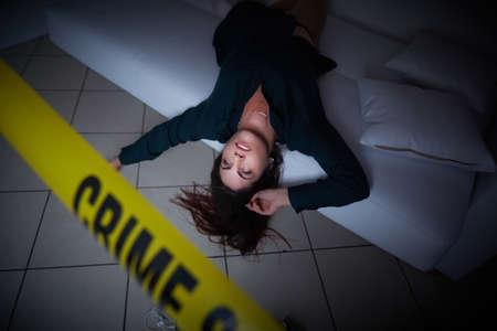 scène de crime - femme liyng morte sur le canapé