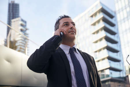 businessman talking to mobile in urban environment