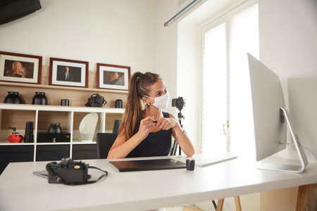 young professional photographer working in home studio durint quarantine for Covid-19 lockdown Stok Fotoğraf