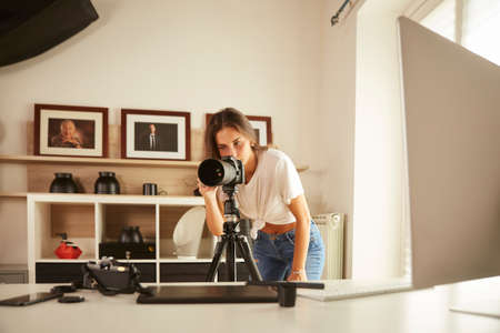 young professional photographer working in home studio