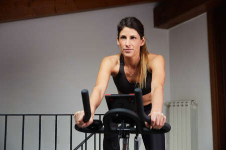 woman spinning at home exercising for their legs and cardio training Standard-Bild