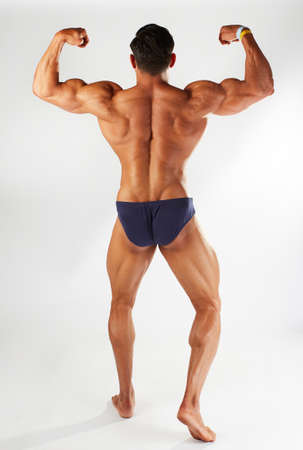 male body builder posing in studio background