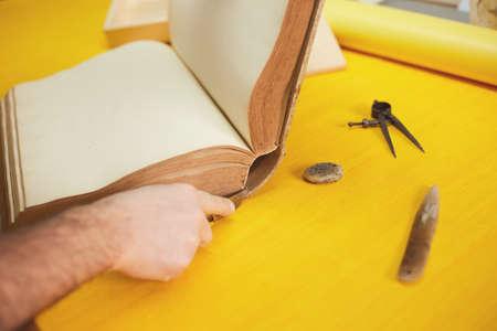 book binder restores old book in craft workshop