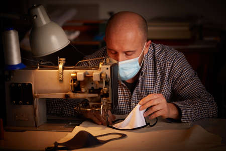 man working with sewing machine doing homemade face mask