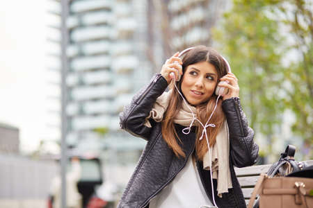 young brunette listening music by headphones in urban environment