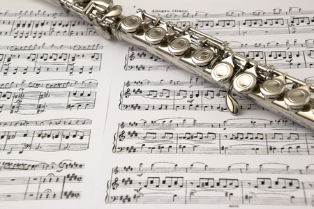 flute key: Flute on flute score background Stock Photo