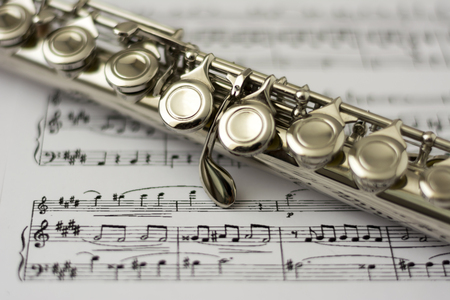 flute structure: Close up flute on flute sheet music background
