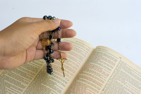 Asian woman hand holding rosary beads closeup and holy bible on background.