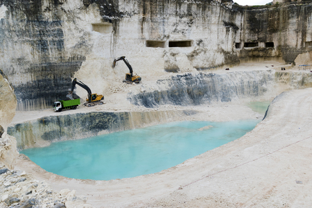 Limestone mining Jedi Hill work site landscape view with light pastel blue pond in the middle at Madura, East Java, Indonesia