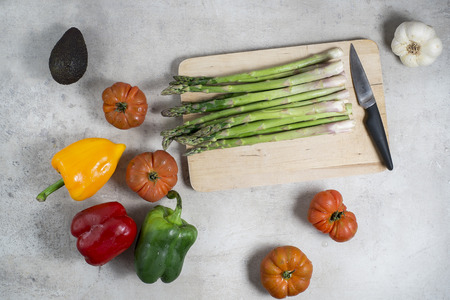 ready to cook food: Fresh vegetables on table tomatoes garlic asparagus avocado green pepper red pepper yellow pepper. Platter and knife ready to preparing the salad. Raw food to cook healthy and diet.