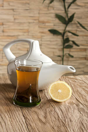 a cup of green tea and a teapot on a background wall with stone cladding