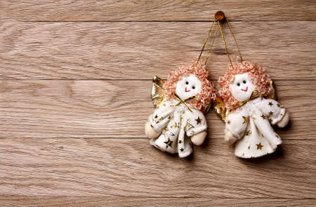 Christmas decoration -  Two angels   hanging over wooden background photo