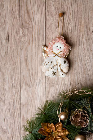 Christmas decoration - angel and wreath  hanging over wooden background