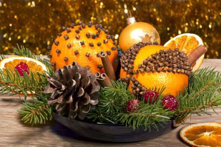 Christmas decorative composition with orange pomanders close ap on a wooden background