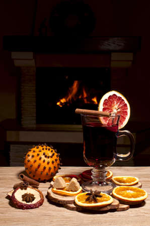 glass of mulled wine on the background of a burning fireplace