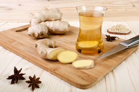 Ginger tea and ginger root on a wooden background Stock Photo - 16449465
