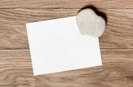 Stone in the shape of a heart and a piece for congratulations on a wooden background photo