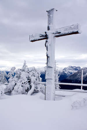 Snow-covered cross on the top of the mountain