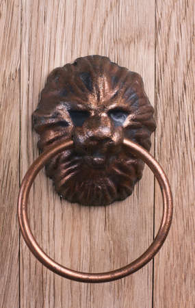 Old door handle, a lions head on a wooden background Stock Photo
