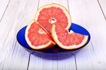 grapefruit in a blue plate on a light wooden background