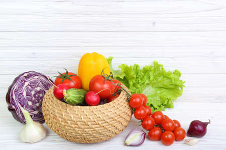 Multi-colored vegetables on a light wooden background