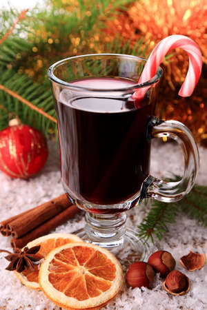 mulled wine with candy stick in the snow