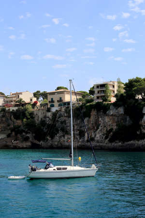 Yacht parked on the background of the rocky shore. Mallorca. Spain Stock Photo