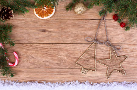 Vintage Christmas decorations on wooden background surrounded by fir branches and snow