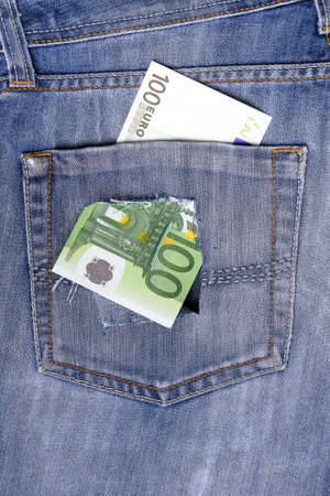 One hundred euro note in the back pocket of jeans full of holes. The concept of poverty, wastefulness.