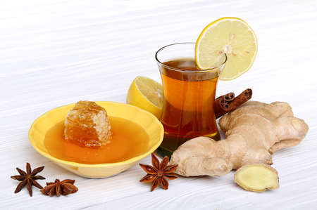 Tea with ginger, honey, lemon and spices on a light wooden