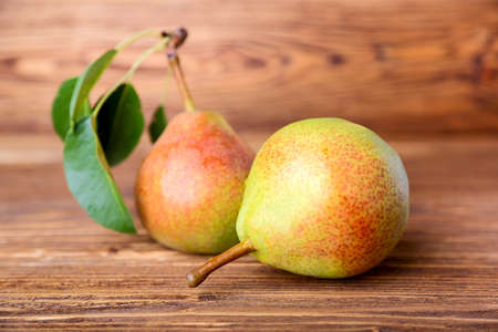 Pears with green leaves on brown wooden background. selective focus
