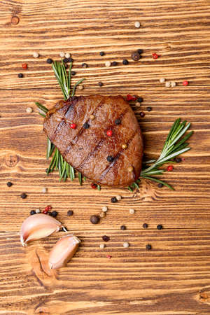 grilled steak and spices on wooden background