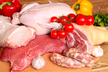 Fresh raw meat - beef, pork, chicken and vegetables on a wooden background Stock Photo