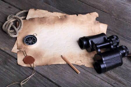 Vintage background, concept of travel - old paper, pencil, compass and binoculars on a wooden background, place for text