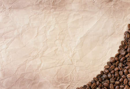Background of black coffee beans and old paper, place for text Stock Photo