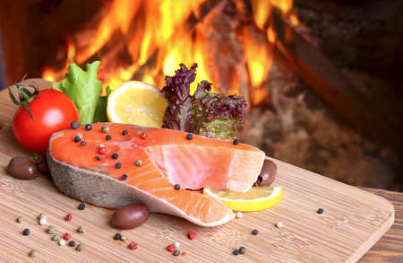 Salmon Steak on a cutting board on a background of a burning flame Stock Photo