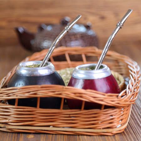 Yerba mate and mate in calabash on a wicker tray, selective focus
