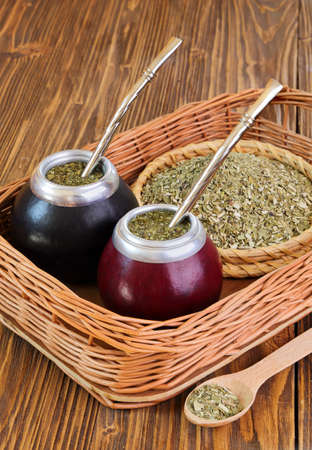 Yerba mate and mate in calabash on a wicker tray on a wooden background photo