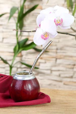 yerba mate: Mate de té en la calabaza y orquídea sobre fondo de pared de piedra