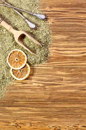 yerba mate: Antecedentes - yerba mate y bombilla en una mesa de madera, espacio para el texto