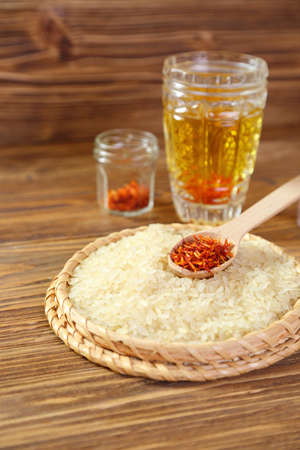 Spoon of dry saffron in a dish with rice photo
