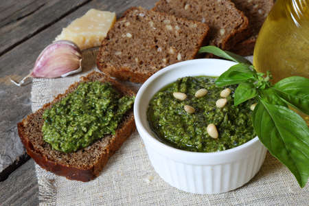 eat smeared: Italian pesto sauce and rye toast on a wooden table Stock Photo