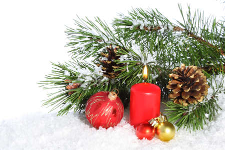 Christmas composition with burning candle and decorations on snow
