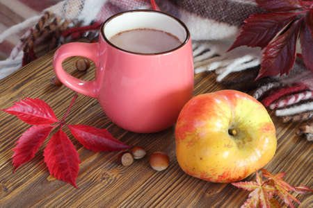 Autumn still life with a cup of cocoa and apple.